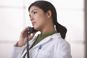 Hispanic doctor talking on telephone