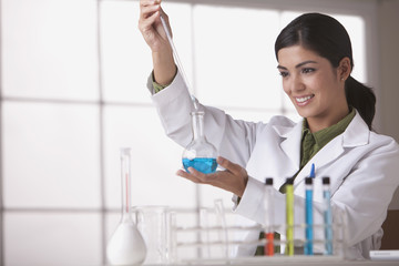 Hispanic scientist holding beaker of liquid