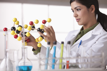 Hispanic scientist looking at molecule model
