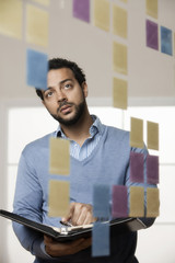 Mixed race businessman looking at sticky notes in office