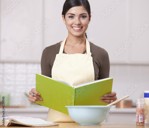 Hispanic woman reading recipe in kitchen