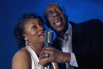 African American couple singing into microphone