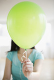 Korean woman holding balloon in front of her face