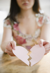 Korean woman holding torn paper heart