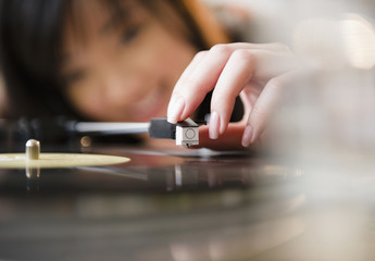 Korean woman putting playing arm on record