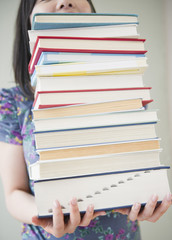 Korean woman holding stack of books