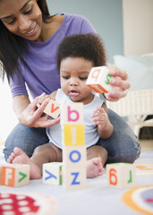 African American mother and son playing with alphabet blocks