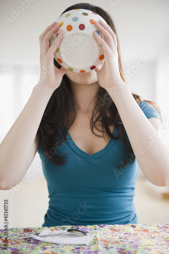Korean woman drinking from bowl
