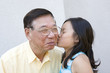 Chinese granddaughter kissing grandfather
