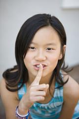 Chinese girl making shhh gesture
