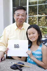 Chinese grandfather teaching granddaughter calligraphy