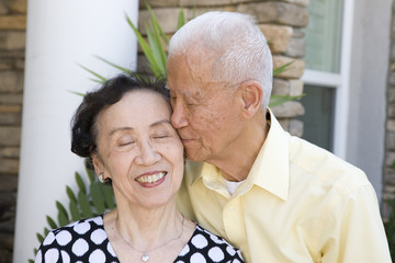 Senior Chinese man kissing wife