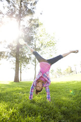 Chinese girl doing cartwheel in grass