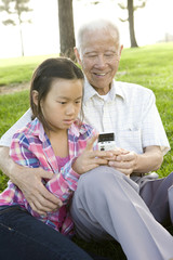 Chinese girl sitting in grass showing grandfather cell phone