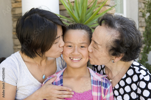 Chinese grandmother and mother kissing daughter