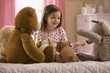 Mixed race girl reading story to stuffed animals