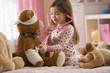 Mixed race girl playing doctor with stuffed animal