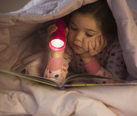 Mixed race girl reading book in bed with flashlight