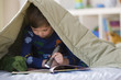 Caucasian boy reading with flashlight underneath blanket