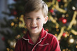 Caucasian boy in pajamas next to Christmas tree