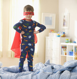 Caucasian boy playing in superhero costume