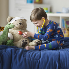 Caucasian boy listening to teddy bear's heartbeat with stethoscope