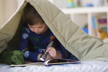 Caucasian boy reading with flashlight underneath blanket