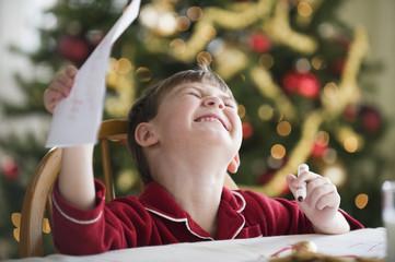 Caucasian boy writing Christmas letter to Santa