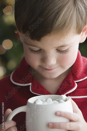 Caucasian boy in pajamas drinking hot chocolate with marshmallows