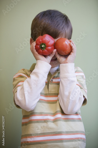Caucasian boy putting vegetables in front of his eyes