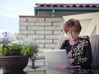 Senior Caucasian woman using laptop on patio