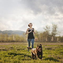 Caucasian woman running in field with dog