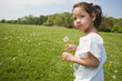 Girl walking in field with dandelion flower