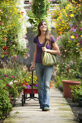 Caucasian woman pulling wagon in plant nursery