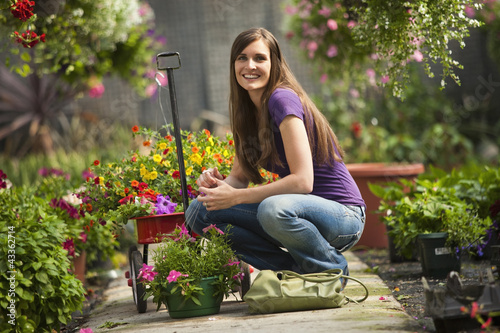 Caucasian woman squatting with flowers in plant nursery