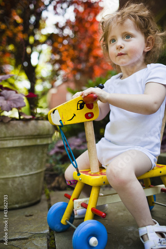 Girl riding wooden giraffe