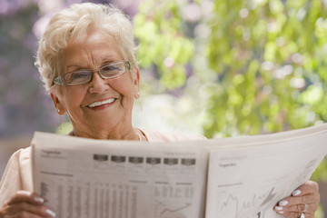 Senior Hispanic woman reading financial newspaper