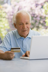 Senior Hispanic man shopping online with credit card