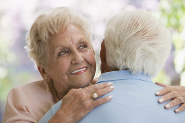 Senior Hispanic woman hugging husband