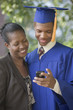 Graduating teenager and mother looking at cell phone