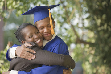 Proud mother hugging graduating son