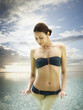 Woman in a bikini standing in the ocean a  tropical luxury resort