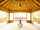 Rear view of woman sitting in lotus position on floor of yoga and meditation pagoda at a luxury resort