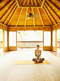 Woman laughing sitting in lotus position on floor of yoga and meditation pagoda at a luxury resort