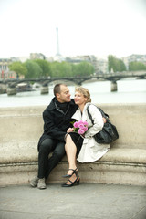 Caucasian couple sitting on bench on bridge
