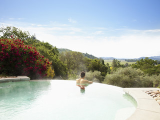 Man at a luxury resort in infinity pool overlooking Napa Valley, California