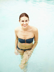 Smiling beautiful woman in a swimming pool at a luxury resort