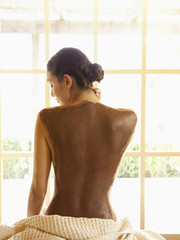 Woman sitting on massage table looking out with mud mask on her back at luxury spa