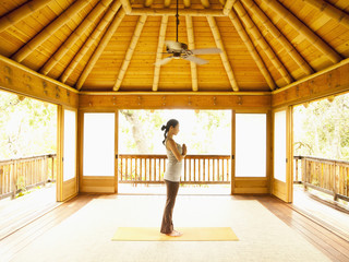 Profile of woman standing in prayer position inside yoga and meditation pagoda at a luxury resort