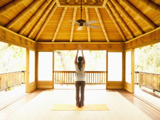 Rear view of woman standing with arms raised inside yoga and meditation pagoda at a luxury resort